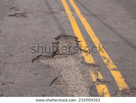 Rough patched roads and potholes in pavement of a city street