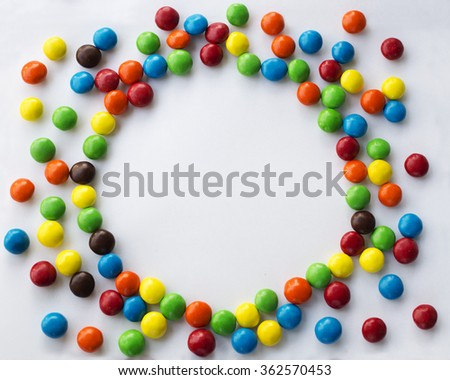 Round frame look like sun of colorful chocolate candies on a white background with space for your text Valentines Day concept