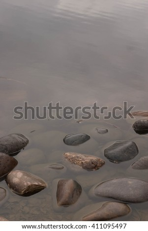 round large rocks laid along the pond in the park