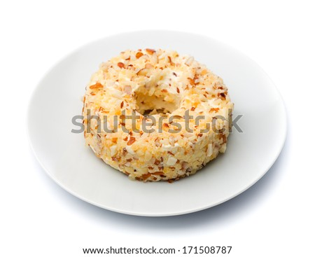 Round sweet cheese with nuts and pineapple on a plate. Isolate on white.