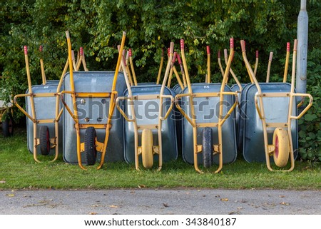 Row of Empty Wheelbarrows on Lawn