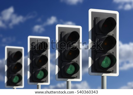 ROW OF FOUR ROAD TRAFFIC LIGHTS SHOWING GREEN