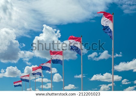 Row of seven Dutch national flags against a sunny cloudy blue sky