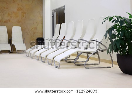 Row of six white comfortable seats in empty room for waiting.