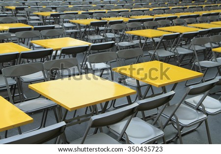 Rows of yellow empty tables and chairs