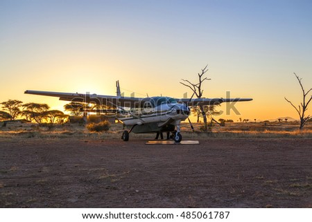 RUAHA, TANZANIA - JUN 7, 2013:  In the morning sun Group of tourists arriving in the Ruaha National Park airstrip, these small airfields are  major hubs for tourism and also the industry supply route.