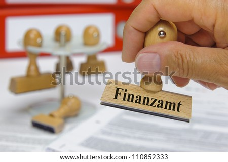 rubber stamp in hand marked with tax office, in german: Finanzamt
