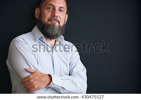 Rugged looking mature man with beard against black textured background