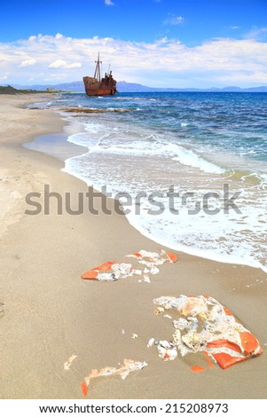 Ruins covered by sand beach with distant ship wreck near Gythio, Greece