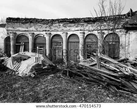 Ruins of old abandoned manor and piles of rubbish in front of it