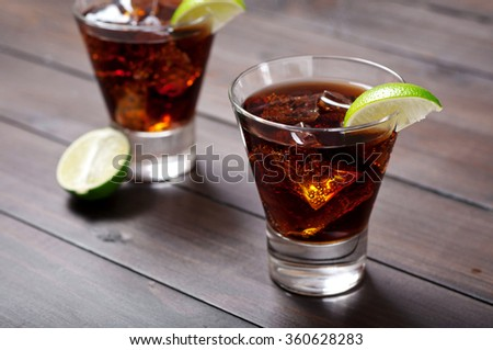 Rum and Cola Cuba Libre with Lime and Ice on wooden table closeup