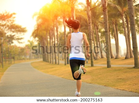 Runner athlete running at tropical park. woman fitness sunrise jogging workout wellness concept.