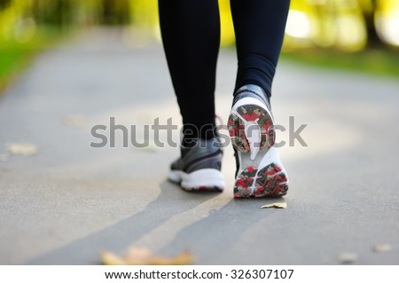 Runner feet running on road closeup on shoe. Woman fitness jog workout, welness concept