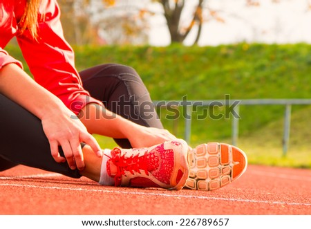 Runner feet running on running track closeup on shoe