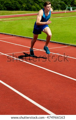 Runner practicing in athletics stadium racetrack.