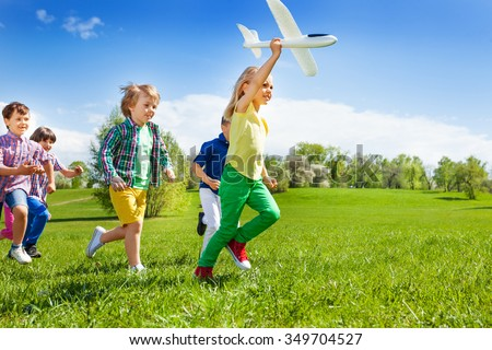 Running kids and girl holding big white airplane toy in the field during summer sunny day