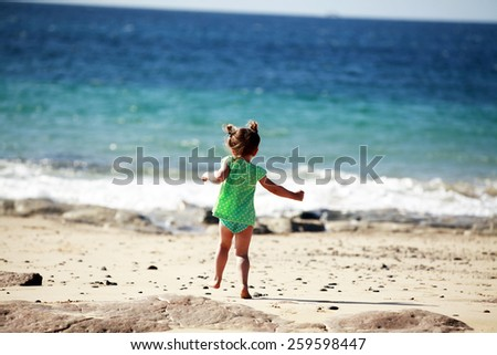 Running little girl on sandy beach