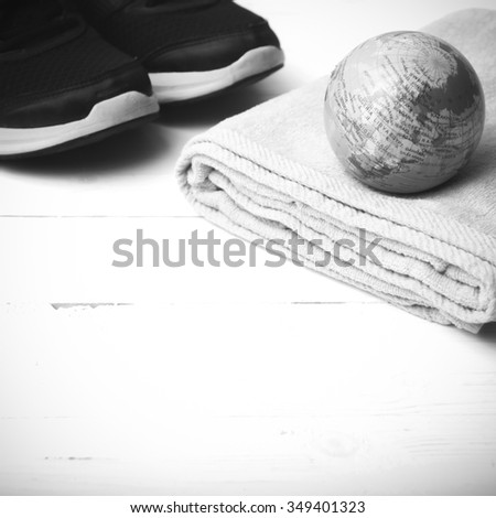 running shoes,towel and earth ball on white wood table concept world healthy black and white tone color style