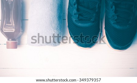 running shoes,towel and orange juice on white wood table vintage style