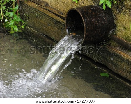 Running spring water from metal tube in the village, summer