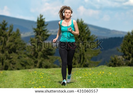 Running woman. Girl jogging on trail in mountains on field with grass in summer sunny day. Fitness. Healthy lifestyle