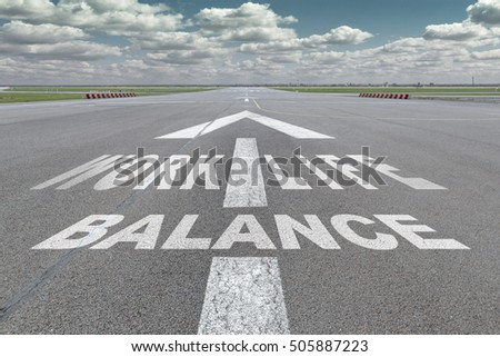 "Runway of airport with arrow guideline and ""work life balance"" letters painted on the surface"