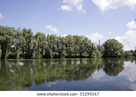 Rural landscape. A reflection of trees is in water of pond.