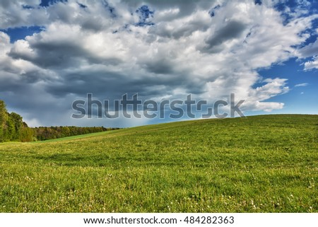 Rural landscape - meadows with blue sky and clouds over them.