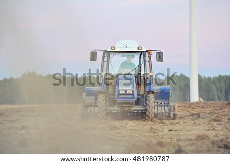 Rural landscape with tractor in the field during sowing grain