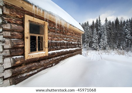 Russia log house in winter, with fir trees in background at Urals, Russia