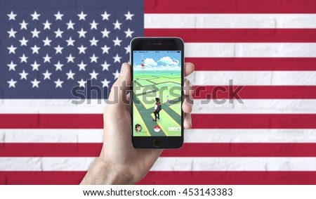 Russia, Moscow - July 15, 2016 : Apple iPhone 6 held in one hand showing its screen with Pokemon Go application. USA Flag Collage.