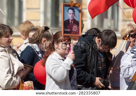 RUSSIA, ROSTOV CITY - MAY 9: Unidentified woman holds a portrait and walks on Victory day parade dedicated to the 70th anniversary of WWII end on May 9, 2015 in Rostov, Russia