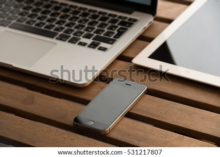 Russia-Samara-12dec-2016 - Apple gadgets on the wooden table - iPad, iPhone 5S Macbook PRO