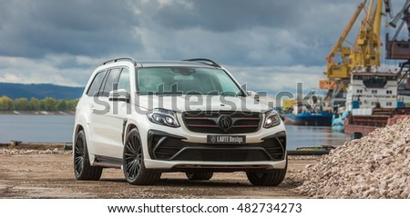 Russia, Togliatti - September 9, 2016: Test drive of Mercedes GLS with tuning kit Black Crystal of LARTE Design Tuning Company. Volga river and color port-cranes in cargo port at the background