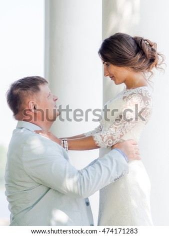 Russian Groom embraces Russian bride on a background of white columns