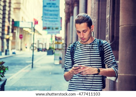 Russian Man traveling in New York, wearing striped long sleeve T shirt, shoulder carrying back bag, standing by wall on vintage street, reading, texting on cell phone, listening music with earphone.