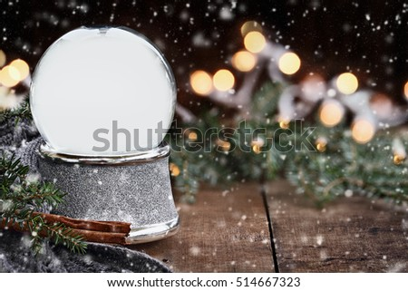 Rustic image of an empty snow globe surrounded by pine branches, cinnamon sticks and a warm gray scarf with gently falling snow flakes. Shallow depth of field with selective focus on snowglobe.