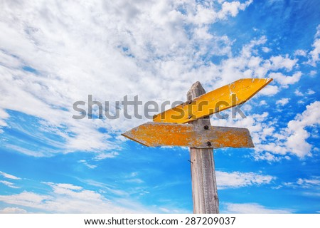 Rustic yellow crossroads sign against a cloudy blue sky.