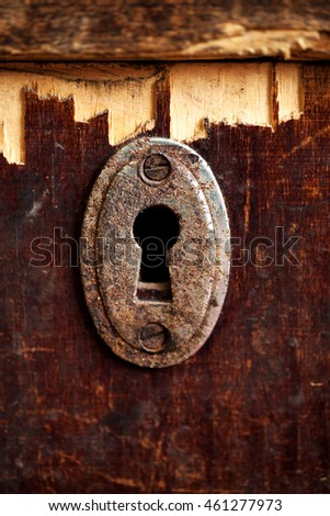 Rusty keyhole in old wooden table, selective focus, vertical