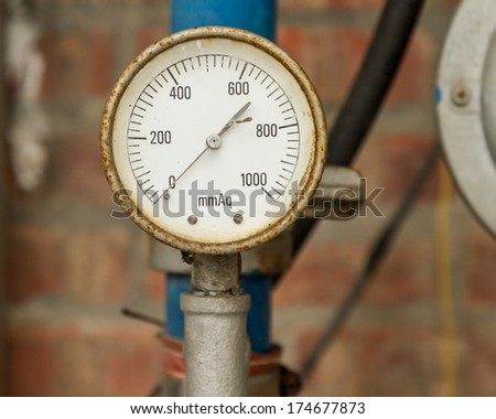 Rusty Pressure Gauge connected to pipes with brick wall behind