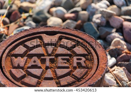 rusty water supply lid on ground