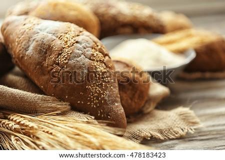 Rye bread with sesame seeds and spikes on a wooden table