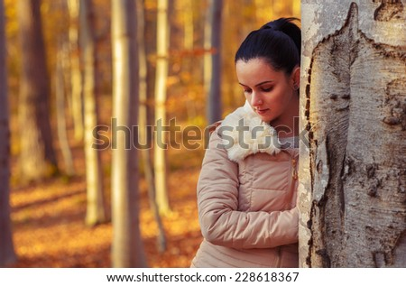 Sad beautiful woman in forest while autumn season