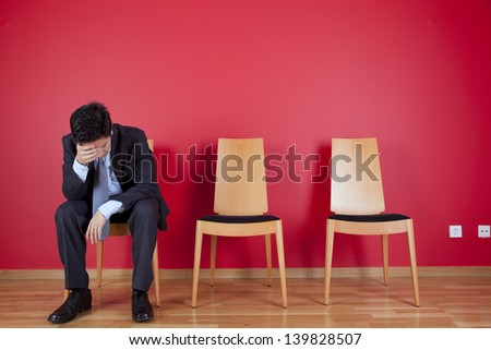 Sad businessman sited next to a red wall