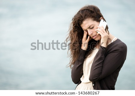 Sad crying woman talking on the phone. Emotional crisis, troubles and love depression concept.