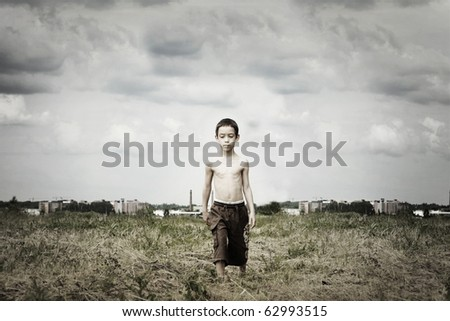 sad kid is walking in the field against ugly industrial background with artistic shadows added