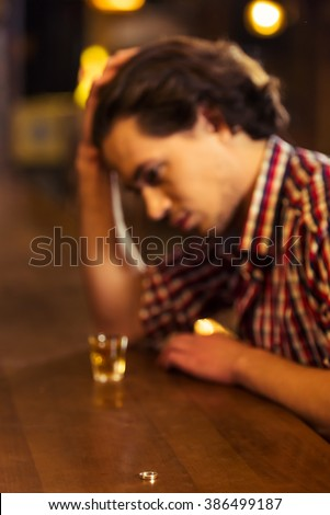 Sad man in casual clothes is leaning on bar counter in pub, a glass of alcoholic beverage near, in the foreground a wedding ring