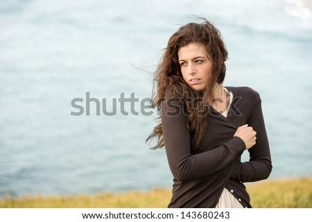 Sad shivery woman in brown sweater jacket hugging herself on late summer cold and windy day on sea background. Sadness, melancholia and heart broken concept.
