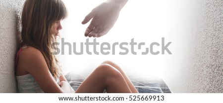 Sad teenage girl sitting on the floor while hand is offering help and support.