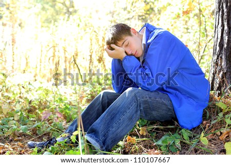 sad teenager sitting in the autumn forest alone
